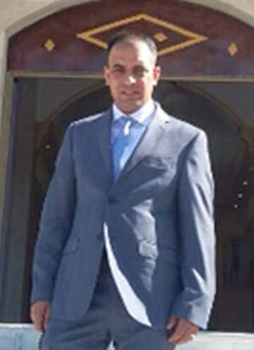 Sadam Issa looks on at the camera in front of an open doorway. He is wearing a grey suit with a white shirt and silver tie.