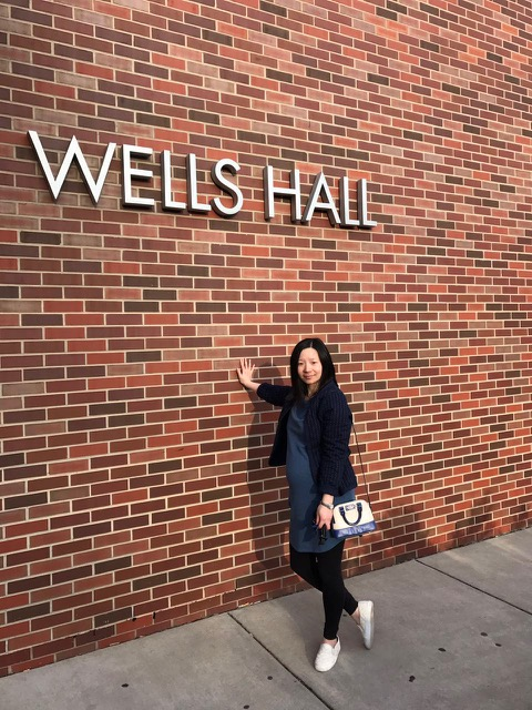 """woman in front of brick wall with """"Wells Hall"""" on it"""