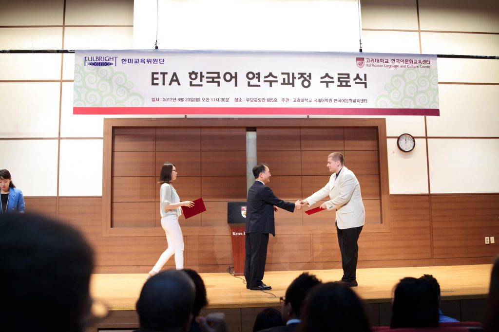 Man in white coat accepting an award on stage