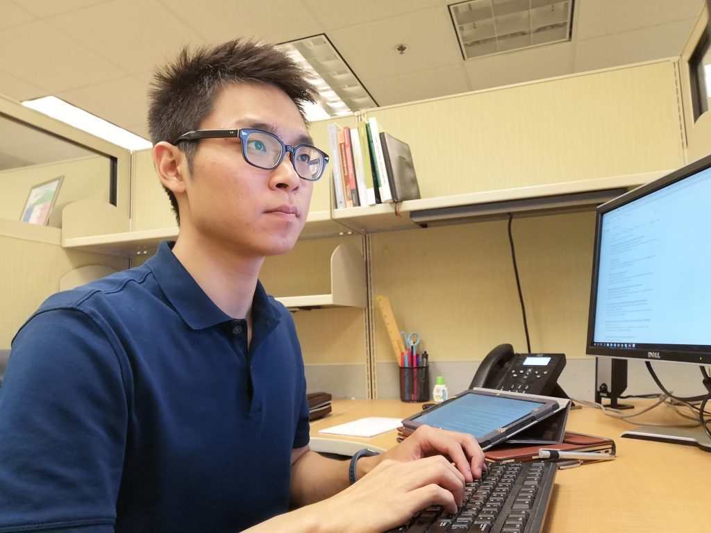Man wearing black rimmed glasses and blue button up shirt is sitting at a cubicle and typing on a computer