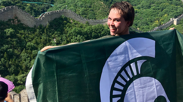 woman with a Michigan State University flag on her back standing in front of the Great Wall