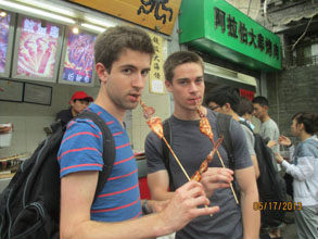 two students eating meat off sticks