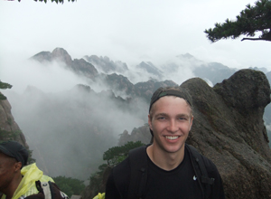 man in baseball cap in front of mountain range