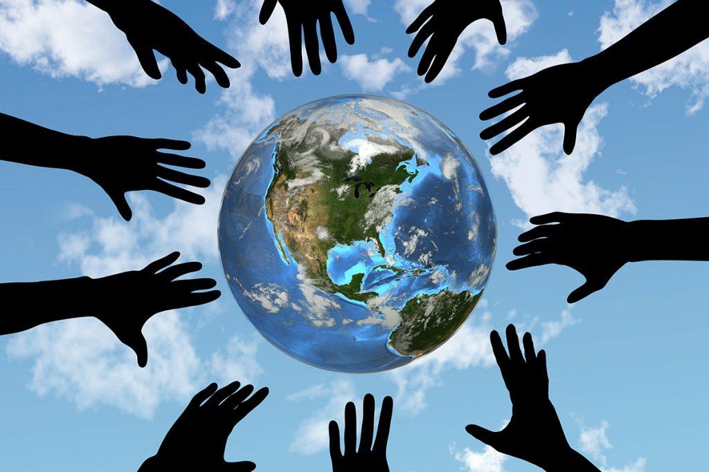 Hands reaching towards a globe