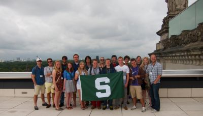 students standing behind a MSU flag