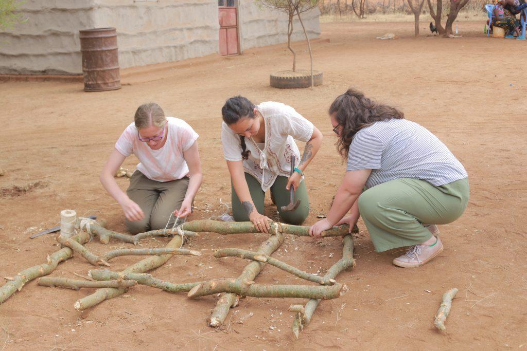 three girls building a raised garden with sticks