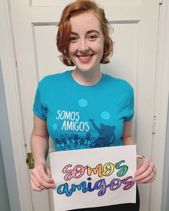 a woman with short hair holding up a sign that is written in Spanish, wearing a blue t-shirt