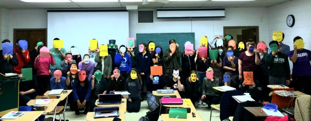classroom full of students wearing paper masks
