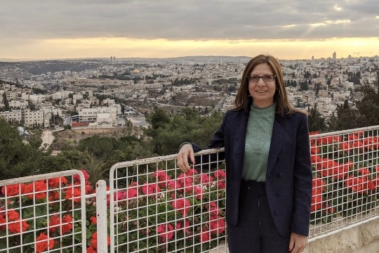 a photo of a woman with brown hair wearing glasses, a navy blue blazer, with a city behind her
